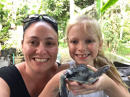 lady and girl holding baby turtle, bali turtle releases